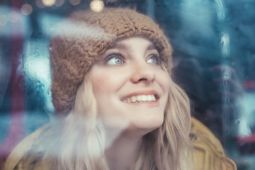 Happy hipster woman looking up from bus window