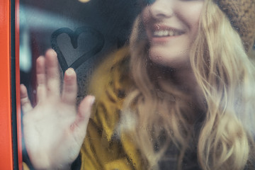Happy hipster woman drawing heart shape on window