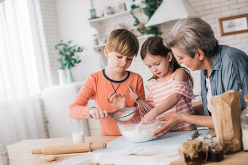 Grandchildren preparing pie with their granny at home