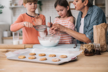 Grandchildren preparing cookies with their granny at home