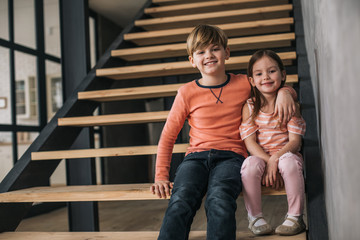 Low angle of children sitting on stairs while situating in granny's house