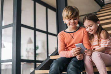 Low angle of children sitting on stairs while holding smartphone in arms