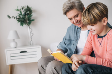 Cropped photo of little boy reading book with his grandmother in house