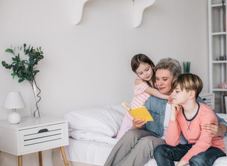 Cropped photo of gray-haired woman reading book for her grandchildren in house