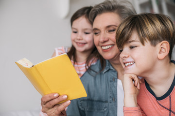 Close up of gray-haired woman reading book for her grandchildren in house