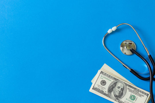Costly treatment. Stethoscope and dollars on blue background