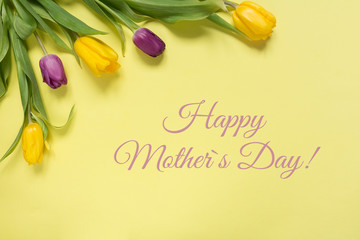 Yellow and purple flowers tulips in a bouquet on a yellow background and the inscription happy mother's day, a festive spring background greeting card