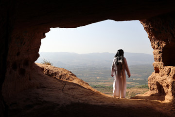 ARABIC MAN LOOKING A VALLEY FROM A CAVE