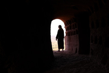 MAN WITH ROBE AND PALESTINIAN SCARF AT THE ENTRANCE OF A CAVE