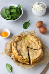 Spinach, chicken and ricotta pie with fresh spinach leaves, ricotta and eggs on a light stone background.