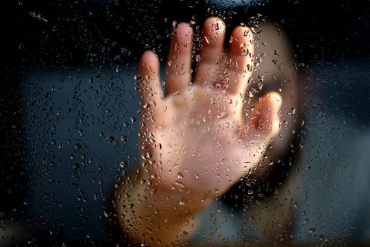 Male hand palm silhouette through the window with raindrops reaching for the glass. A request for help, depression blurred bokeh background