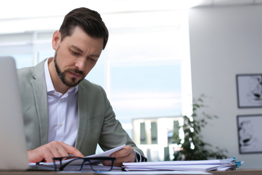 Businessman working with documents at table in office. Space for text
