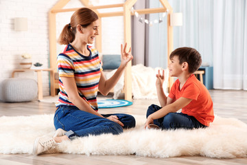 Hearing impaired mother and her child talking with help of sign language indoors
