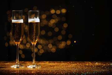 Glasses of champagne and golden glitter on table against blurred background. Space for text