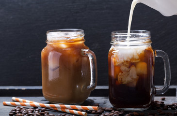milk pouring into jar of iced coffee