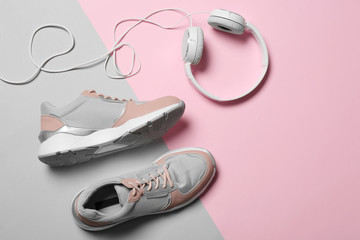 Wall Mural - Flat lay composition with pair of sport shoes and headphones on color background. Space for text