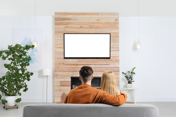 Couple watching TV on sofa in living room with decorative fireplace