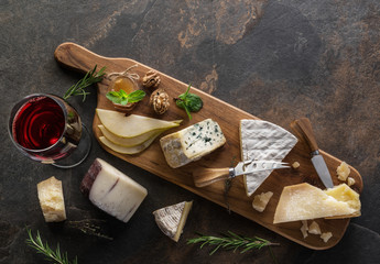 Wall Mural - Cheese platter with organic cheeses, fruits, nuts and wine on stone background. Top view. Tasty cheese starter.