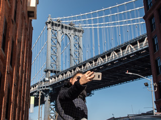 Young woman taking picture at Manhattan bridge from road on sunny winter day. New York, USA