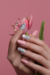 Nails  Art Design. Hands With pink Manicure On pink Background. Close Up Of Female Hands With Trendy pink Nails with spring flower.
