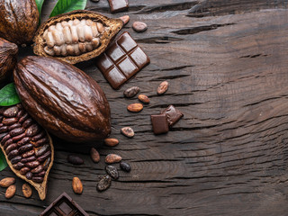 Cocoa pod, cocoa beans and chocolate on the wooden table. Top view.