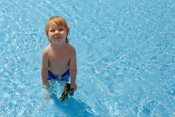 Little relaxed fair toddler boy with goggles in the warm water of swimming pool