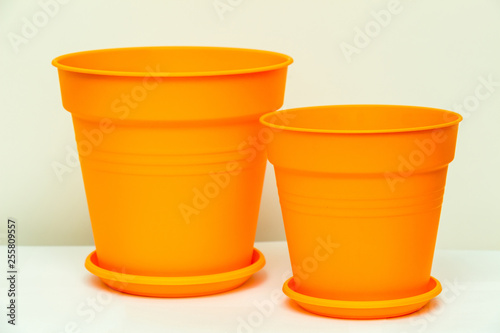 Bright orange flower pots made from plastic for growing indoor plants with stand plates and drainage holes close-up on a white background  sc 1 st  Fotolia.com : orange flower pots - startupinsights.org