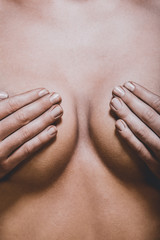 Close view of woman breast covered by hands. Plastic surgery.