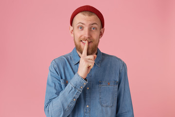 Studio portrait of a bearded guy in denim shirt smiling showing silence gesture, asks to keep secret putting fore finger on the lips, isolated over pink background