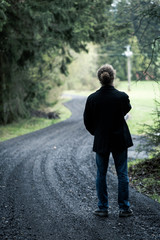 Young man standing on road at end of dark forest