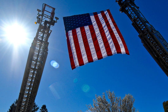 American flag flown from fire truck ladders
