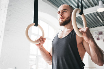 Male athlete holding gymnastic rings at gym. Fitness man is hanging on gymnastics rings in sport hall