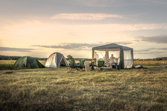Camping site camping tents on summer field sunset sky during camping holidays