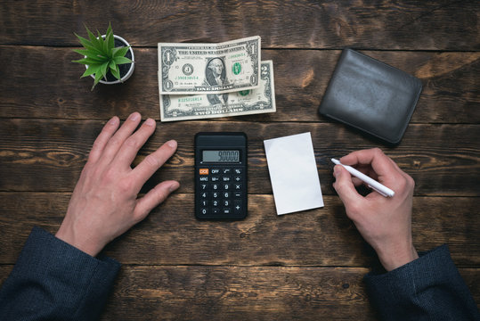 Business man is counting his last dollars from an empty wallet. Tight of money. Lack of money. Financial problems. Bankrupt. Pay the debts concept.