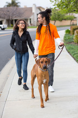 Young couple walking their dog outside