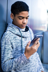 A black man uses a mobile phone. Teen sitting on the stairs playing a game on the smartphone. Afro american boy is writing a message.