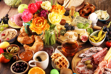 breakfast on table with bread buns, croissants, coffe and eggs