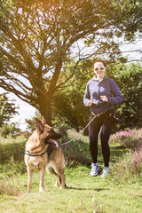 Active woman with dog oudoors at summer time