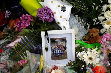 A picture is seen among the flower tribute at a memorial site for victims of the mosque shootings, at the Botanic Gardens in Christchurch