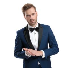 sexy guy in tuxedo rubbing his hands