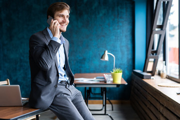handsome businessman in suit standing and talking on smartphone