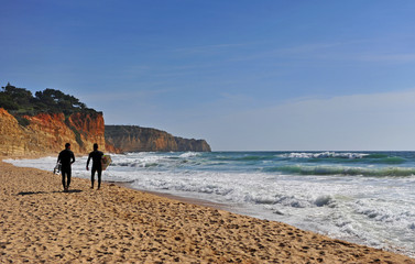 Foto op Canvas Marokko Two men going for surfing on Lagos beach, Portugal