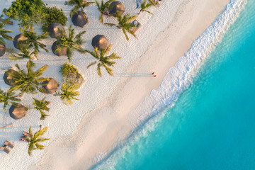 Fotobehang Zanzibar Aerial view of umbrellas, palms on the sandy beach of Indian Ocean at sunset. Summer holiday in Zanzibar, Africa. Tropical landscape with palm trees, parasols, white sand, blue water, waves. Top view