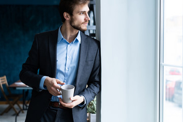 Happy attracive young businessman drinking coffee in office.