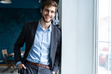Confident professional handsome businessman standing near window in his office