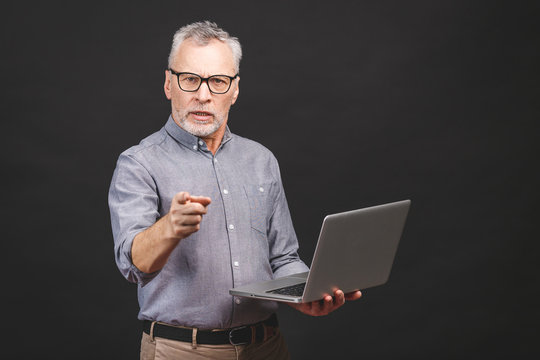 Portrait of aged senior businessman boss furious shouting and gesturing upset and mad in Managing and Stress Problems at Work isolated against black background.