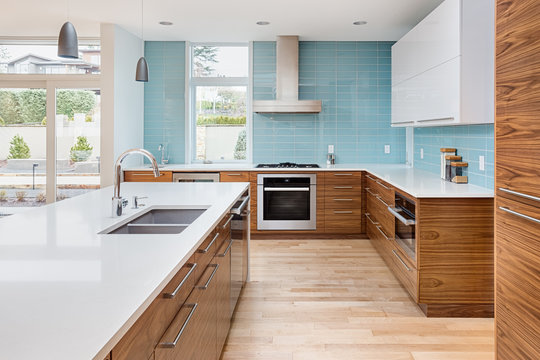 Contemporary Kitchen in New Luxury Home with Large Island, Two Sinks, and Counter to Ceiling Backsplash