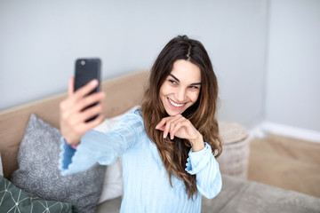 Beautiful young woman taking selfie at home.
