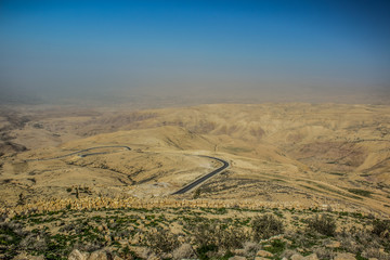 panoramic desert scenery landscape in Jordan holy mountain Nebo aerial photography with lonaly narrow curved road through dunes and horizontal board between foggy ground and blue sky, copy space