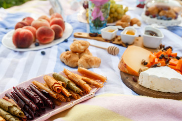 Summer picnic blanket with tasty food and snacks on it. Summer weekends